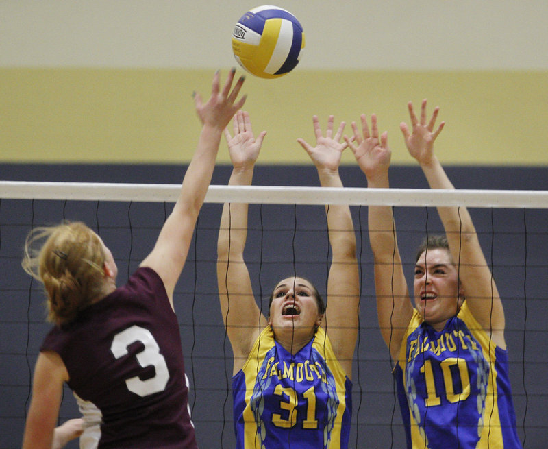 Maggie Bradley, left, of Greely goes for a spike while defended by Falmouth's Jenna Serunian, center, and Jackie Keroack during Falmouth's volleyball victory Thursday.