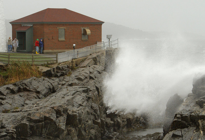 Spectators watch waves crash ashore at Portland Head Light in Cape Elizabeth during Friday's nor'easter. Winds gusting to 50 mph downed trees and caused power outages, and leaf-clogged storm drains resulted in minor street flooding across southern Maine.