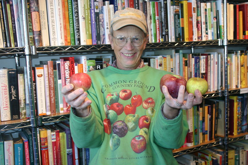 John Bunker shows off a Fameuse, a Macoun and a Gray Pearmain apple while stopping at Rabelais books in Portland to drop off rare apples distributed as part of the Out on a Limb CSA.