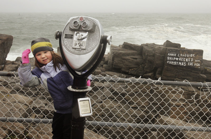 Jenna Bowie-Haskell, 4, of South Portland hangs on to a coin-operated viewer while checking out the surf Friday at Fort Williams Park with her father, Nick Bowie-Haskell.