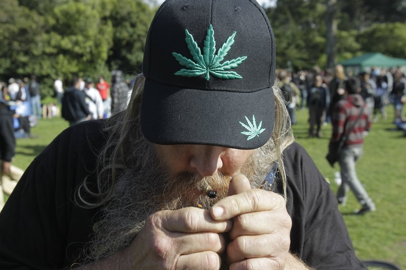 A man smokes marijuana at Golden Gate Park in San Francisco as part of a civil protest last spring. A measure on California's ballot would let adults possess and grow the drug. Federal officials, however, say they would ignore such a state law and 'vigorously enforce' their own ban.