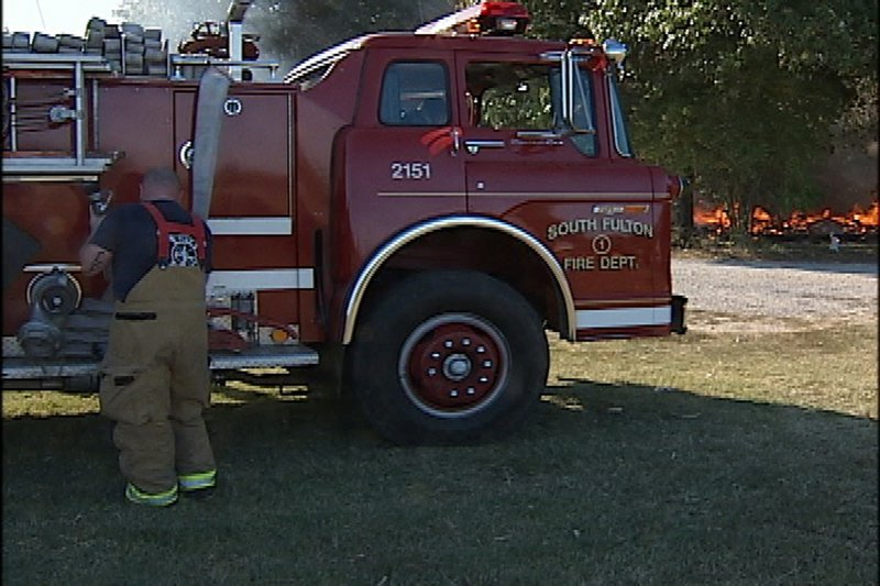 A photo taken from a videotaped image shows firefighters preparing to leave the area as Gene Cranick's home burns in South Fulton, Tenn., on Sept. 29. Local firefighters let Cranick's mobile home burn to the ground because the Cranick family hadn't paid an annual $75 fire protection fee, authorities said.