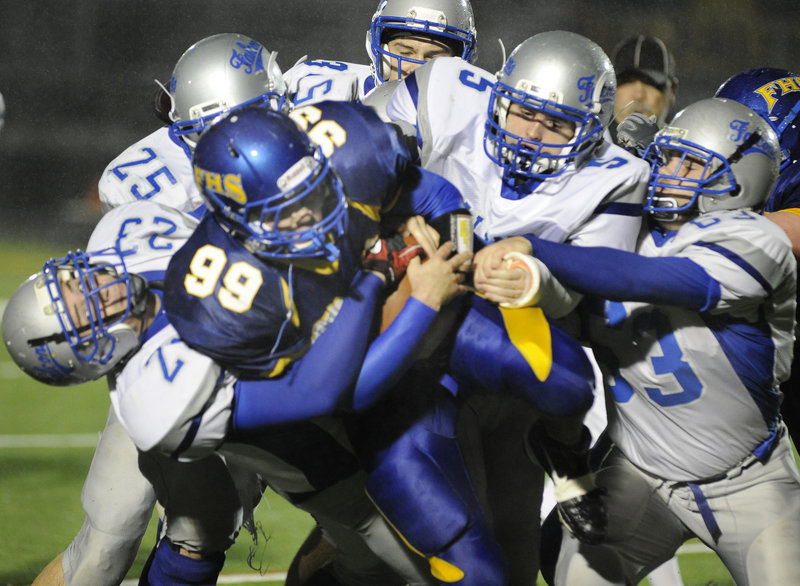 Storm McGovern of Falmouth has no room to run Friday night while looking for yardage against a swarming Mountain Valley defense. Falmouth was held to 12 rushing yards against the undefeated Falcons, who pulled away in the fourth quarter to put the finishing touches on a 38-0 victory.