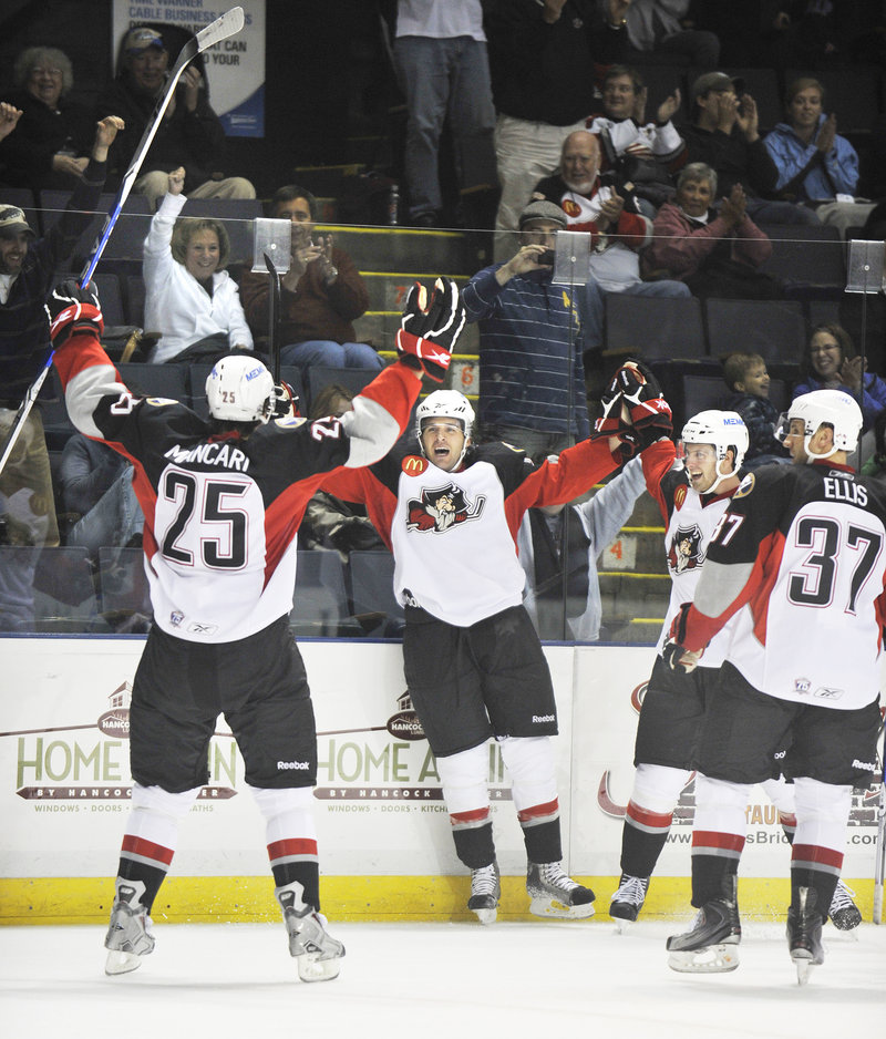 The Pirates celebrate after Dennis McCauley, center, scored Portland's third goal with 2.6 seconds remaining in the second period. McCauley was assisted by Mark Mancari, left.