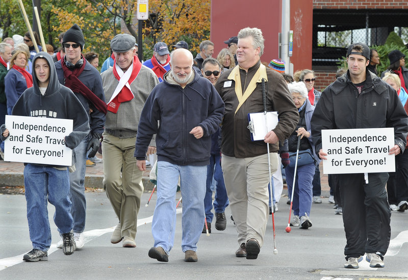 Actor and entertainer Tom Sullivan, third from left in gray cap, and Jim Phipps, fifth from left, executive director of The Iris Network, lead the annual White Cane Awareness Walk in Portland on Saturday. Participants raised awareness for the visually impaired as they walked a loop through downtown that started and ended at the Maine State Pier.
