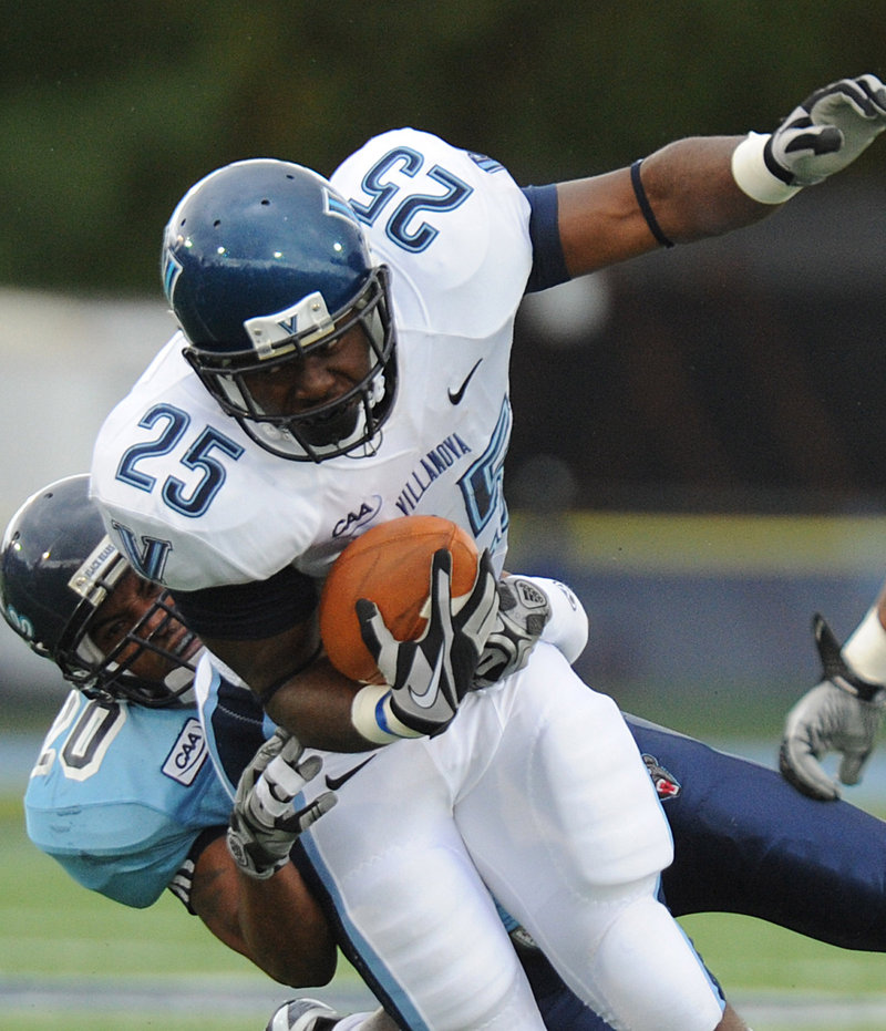 Villanova running back Aaron Ball drags Maine defensive back Steven Barker during Saturday's game in Orono. The Wildcats rolled past the Black Bears, 48-18.