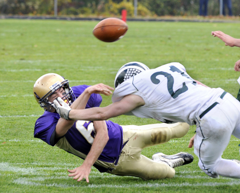 Peter Gwilym of Cheverus gets the ball off just in time to complete a pass Saturday while being taken down by Nick Adkins of Bonny Eagle during Cheverus' 23-20 victory at home.