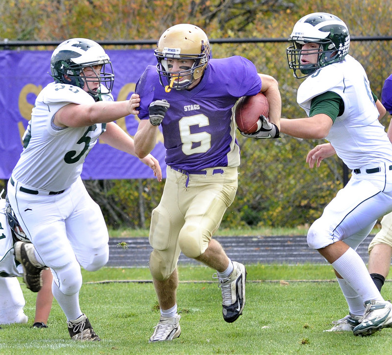 Cheverus quarterback Peter Gwilym looks for room to run Saturday between Andy Martel, left, and Jeff Amell of Bonny Eagle during their Western Class A showdown at Cheverus High. Cheverus won, 23-20.