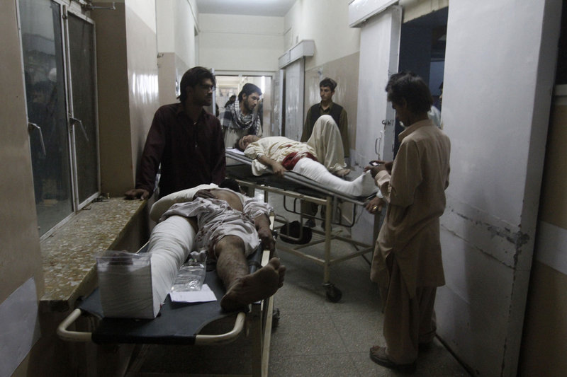 The Associated Press Men injured in a blast are brought to a hospital in Kandahar, Afghanistan, on Saturday – one of several attacks in the city.