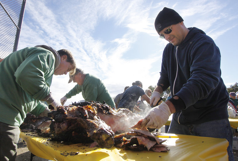 Matt Gallucci, right, a volunteer from Century 21 and Atlantic Realty, carves the ox roast with help from John Edmondson, left, a volunteer from the Stage Neck Inn.