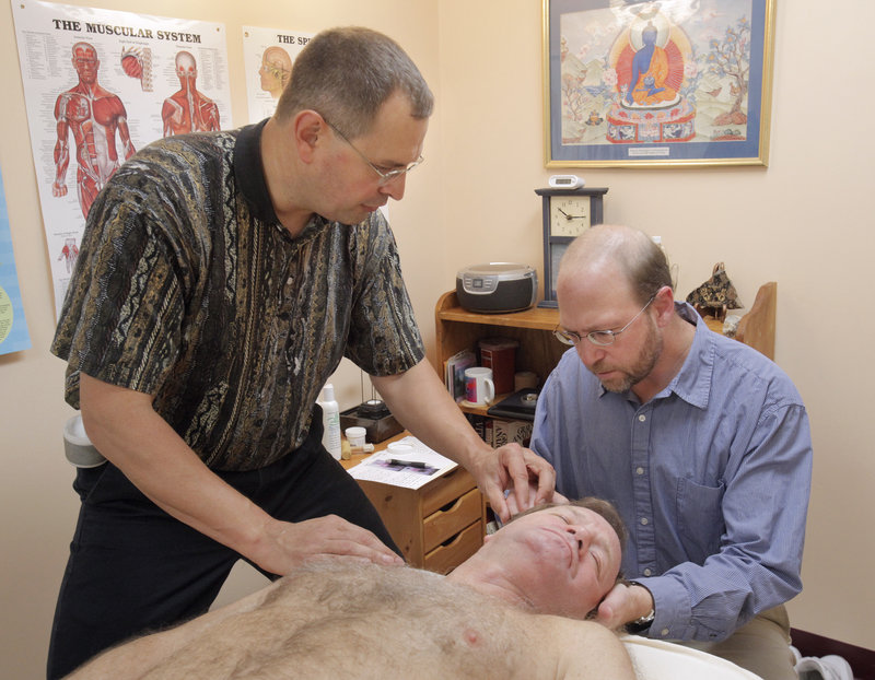 Reporter Ray Routhier, right, learns about massage therapy from Walter Selens in Portland. Selens has been a licensed massage therapist for 22 years.