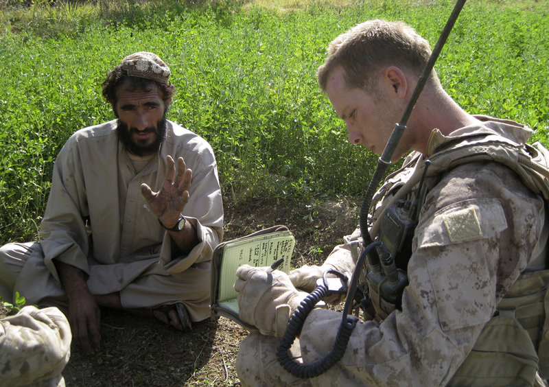 Sgt. John Gabbard talks to a resident of Marjah, Afghanistan, during a patrol. In this southern Afghan town American troops don't have to go far to find the insurgency. Finding insurgents is another story.
