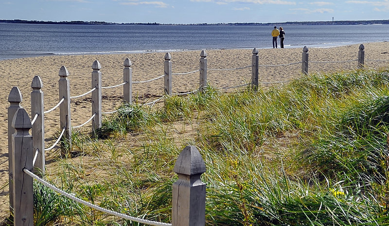 Bob Gray of Arizona and his daughter, Maine resident Lynne Winans, enjoy some solitude Monday on Old Orchard Beach near a protected area of dune grass. The town's dune restoration and protection project has helped preserve delicate ecosystems along the beaches.