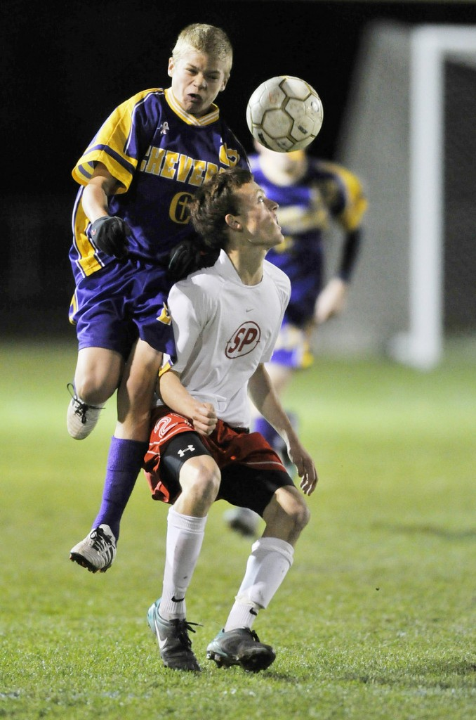 Will Bushey, right, of South Portland uses his head to control the ball as Sterling Weatherbie of Cheverus makes a challenge during Monday's game in South Portland. The Red Riots ended the regular season with a 3-0 victory.