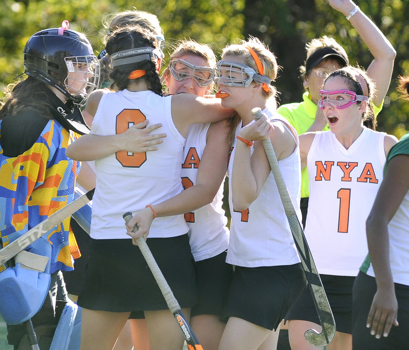 The stoic expression of Waynflete keeper Kailina Mills, left, contrasts with the celebration of NYA players left to right, Katherine Millett, Megan Fortier, Hannah Hearn and Sasha McLean on Millett's first goal Tuesday in Yarmouth.