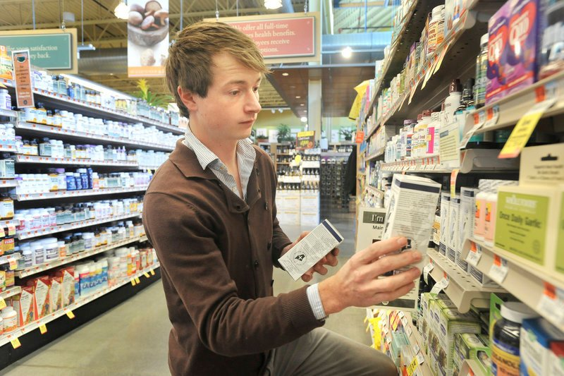 Geo Johnston, operations director at Maine Medicinals, stacks boxes of the Dresden company's products on the shelves at Whole Foods Market in Portland. Maine Medicinals, which makes an organic antioxidant called Anthoimmune, has received a $24,000 loan from Whole Foods.