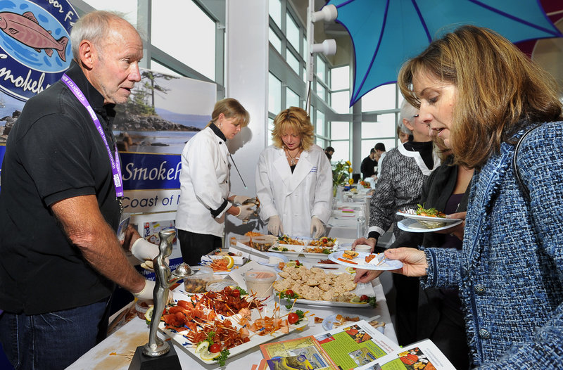 Joel Frantzman, left, owner of Sullivan Harbor Farm Smokehouse in Hancock, offers smoked seafood to Michelle Howard of Cape Elizabeth during the Harvest on the Harbor festival at Ocean Gateway on Thursday.