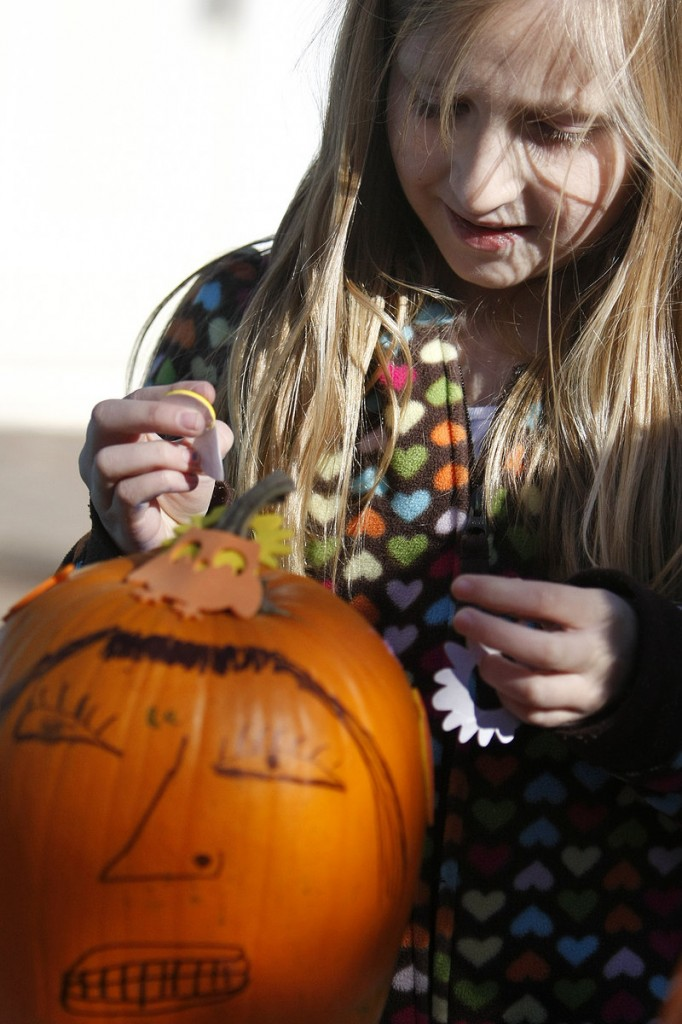 Briana Simpson, 9, of Wells decorates a pumpkin at Cafe Amore on Saturday.