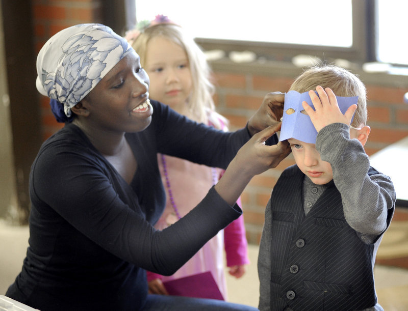 Judith Abdalla, a student in the PATHS early childhood occupations program, fits a mask on Shamus Colson, 4, as Charlotte Murray, also 4, watches during a class Monday.