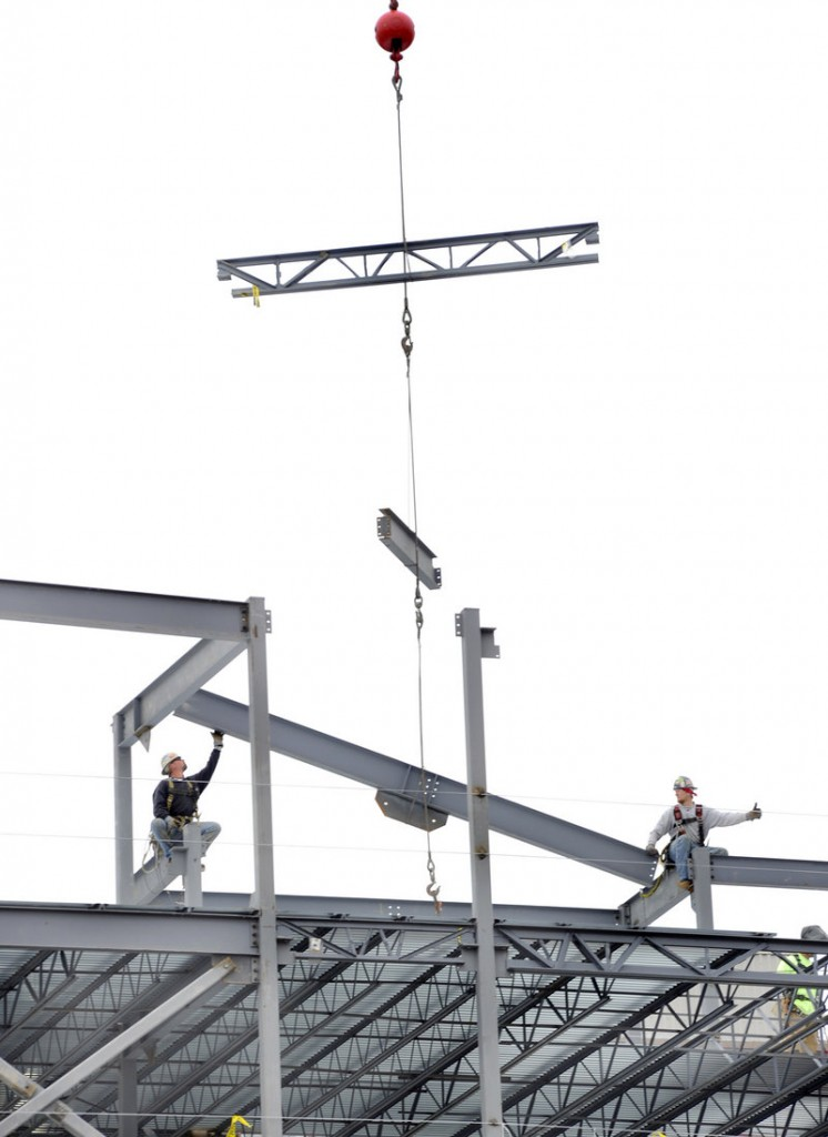 Iron workers Dillon Nutting, left, and Danny Twombly connect sixth-floor steel beams at the former Jordan's Meats site in Portland on Monday. The new building will house a hotel, restaurant and condos.