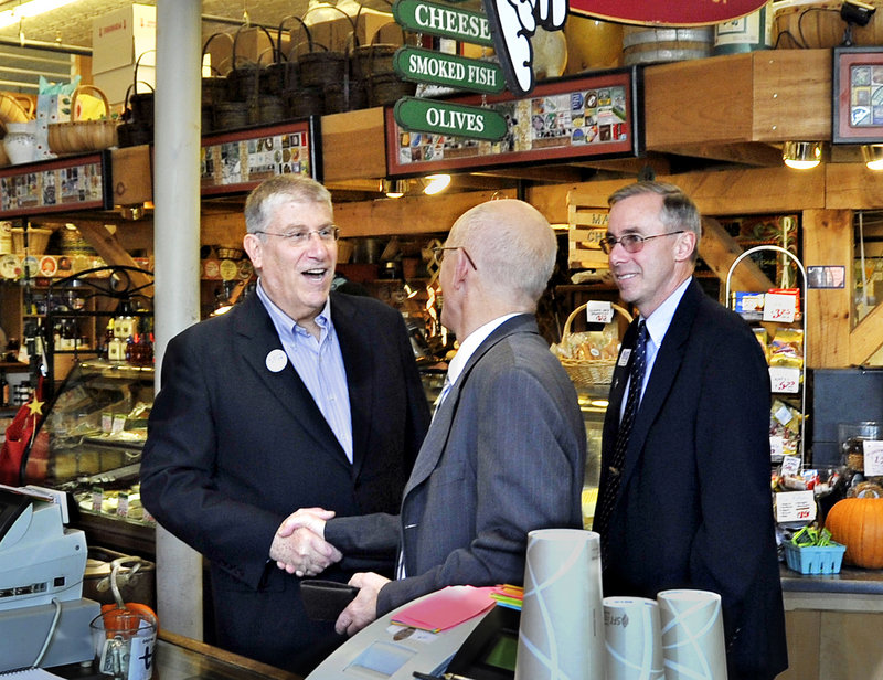 Eliot Cutler, left, greets a patron at the Public Market House on Monument Square as he makes the rounds Tuesday with Ed Suslovic, right, a former Portland mayor who's running for the District 3 City Council seat.