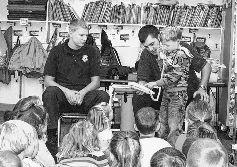 Standish firefighters Will Flanders, left, and Adam Royer show kindergarten student Darren Haskell how to call 911 during a recent fire safety event at Edna Libby Elementary School in Standish.