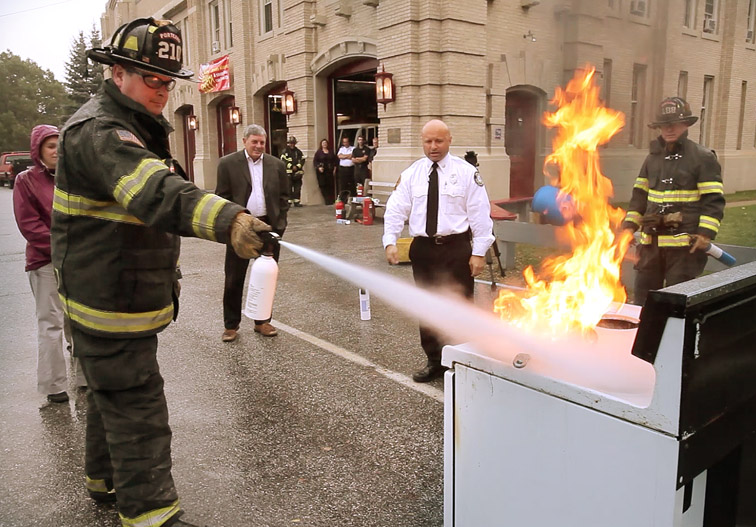 Firefighter Randy Stewart demonstrates how to use a fire extinguisher to put out a stove fire at Central Station in Portland today as part of Fire Prevention Week.