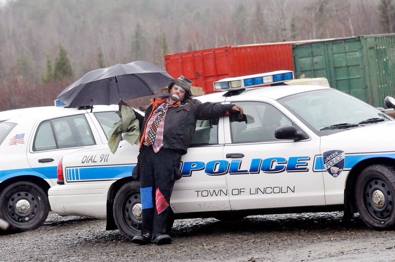 Staff Photo by Shawn Patrick Ouellette: Protester Don Thomas of Lincoln who dressed as a clown named Scruffy stands near a police car as police were arresting protesters who blocked construction vehicles at the Rollins wind energy project in Lincoln Monday, Nov. 8, 2010. Thomas was with Friends of Lincoln Lakes.