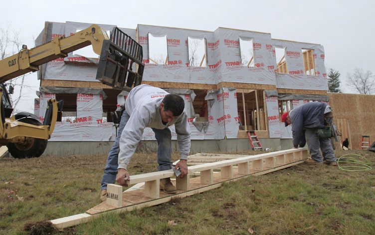 Builders nail together a roof panel for a home under construction in Derry, N.H. Home prices are falling faster in the nation's largest cities, and a record number of foreclosures are expected to push prices down further through next year.