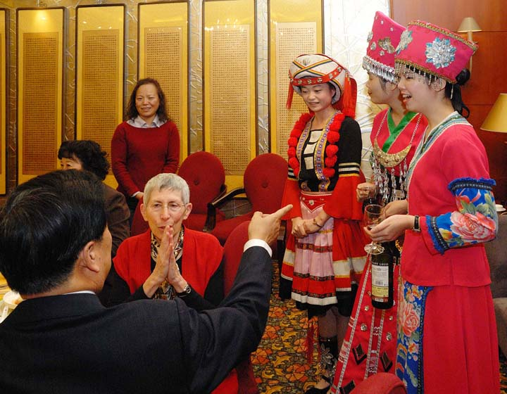 Theodora Kalikow (seated, center), president of the University of Maine at Farmington, listens to an explanation of Yao minority customs as described by her host, Hou Yibin, vice president of Beijing University of Technology, at a banquet honoring BJUT's friendship with UMF.