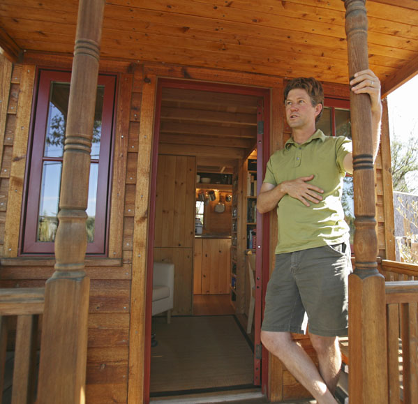 Jay Schafer, owner of Tumbleweed Tiny Houses, stands on the front porch of a tiny house he built for himself in Graton, Calif. Schaefer, who lived in a 89-square foot house with his wife before his son was born last year, builds houses that are smaller than most people's living rooms.