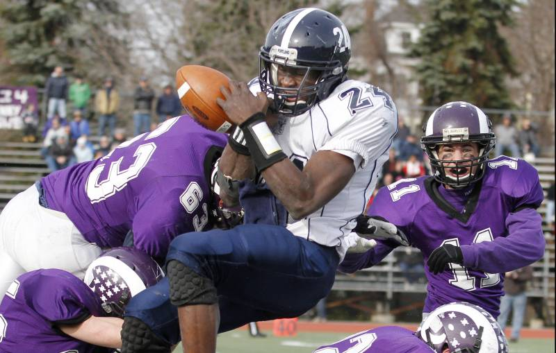 Imadhi Zagon of Portland fumbles Thursday while absorbing a hard hit from Jake Totman, 63, of Deering. Also in on the play for the Rams are Trey Thomes, 25; Devon Fitzgerald, 32; and Matt Flaherty, 11. Deering won the Thanksgiving Day game, 35-14.