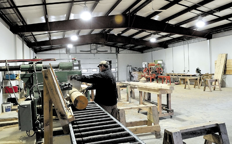 Roland McKenna operates a rebuilt saw Wednesday at the new mill building at Hilltop Log & Timber Homes in Sidney. Fire destroyed the original building last May.