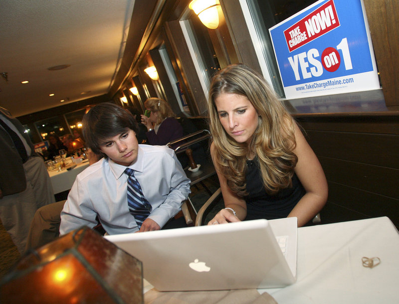Sam and Caity Barber check the results of the Oxford County casino vote Tuesday evening during a reception in Portland. They are the children of Steve Barber, president of Black Bear Entertainment, the casino developer.