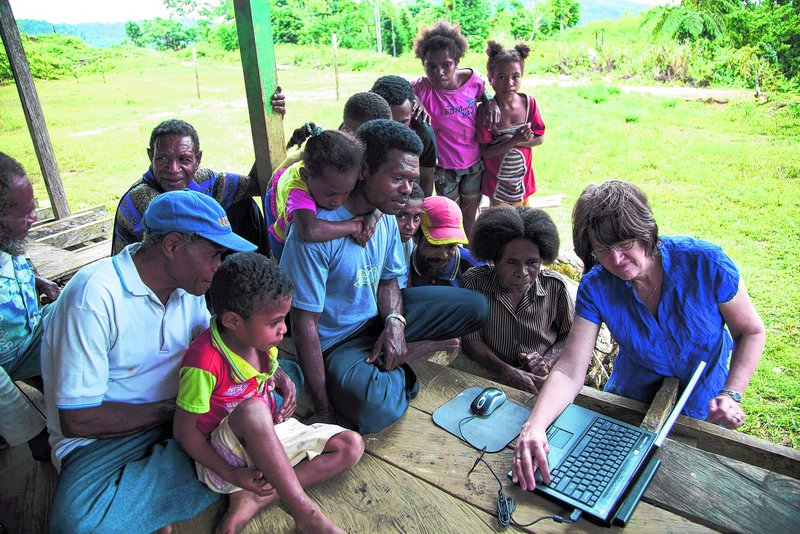 Mandowen, seated at center with his daughter's arms around his neck, joins fellow villagers on a remote island in Indonesia to watch Linda Jones, right, demonstrate how to transmit Bible translations in their language.