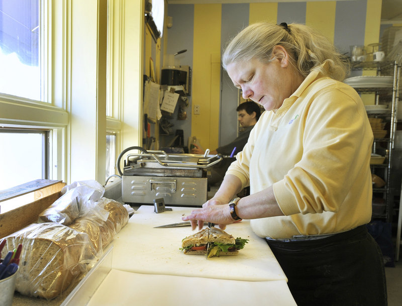 Jane Chilton cuts a sandwich she had just prepared for a customer at Market Day sandwich shop in Kennebunk. Chilton and her partner, Peggy Wagor, own the popular shop, which also features a good selection of cheeses and wines.