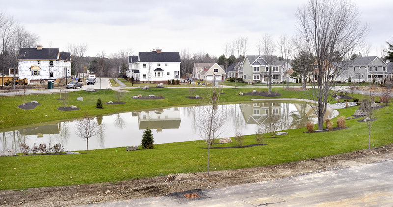 New and existing housing units are reflected in a pond at Dunstan Crossing in Scarborough. It s a viable alternative for people who want to live in a place that integrates housing density, open space and a walkable community, but don't want to live downtown, one expert said.