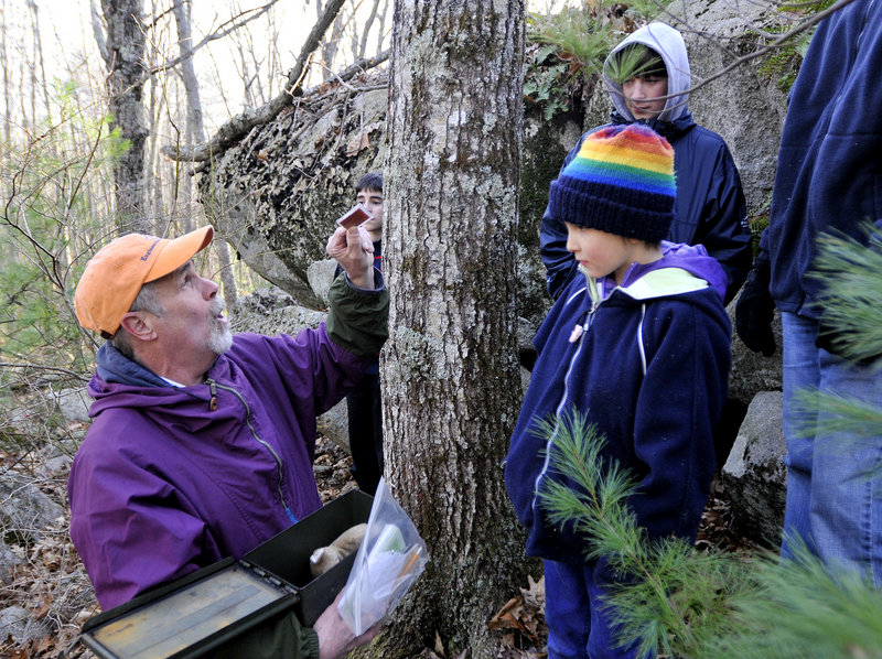 Paul Gadbois shows Gaia Ayres, 8, of Saco and others in the group a coin they found in a geocache during a walk through the sanctuary in Biddeford on Sunday.