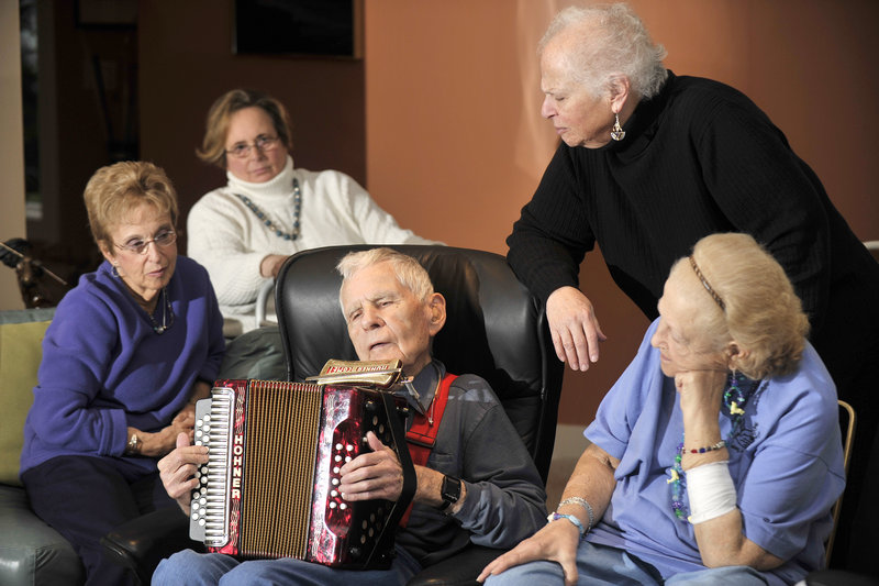 Ninety-year-old Jim Conley, center, plays the accordion and harmonica at Monday's gathering of the Beacon Club, a support group for blind or visually impaired people from Greater Portland. The musician is surrounded by fellow club members and volunteers, from left, Ruth Cohen, Roberta Fishman, Jane Snerson and Gloria Lyons.