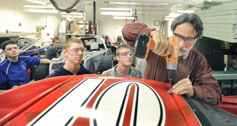 "Instructor John Kraljic, right, leads a Falmouth High School advanced engineering class that's designing and building an electric race car. ""I absolutely love building and machining stuff,"" said senior Sarah Collmus, one of three girls in the class. ""I can't wait to drive one of the cars."""