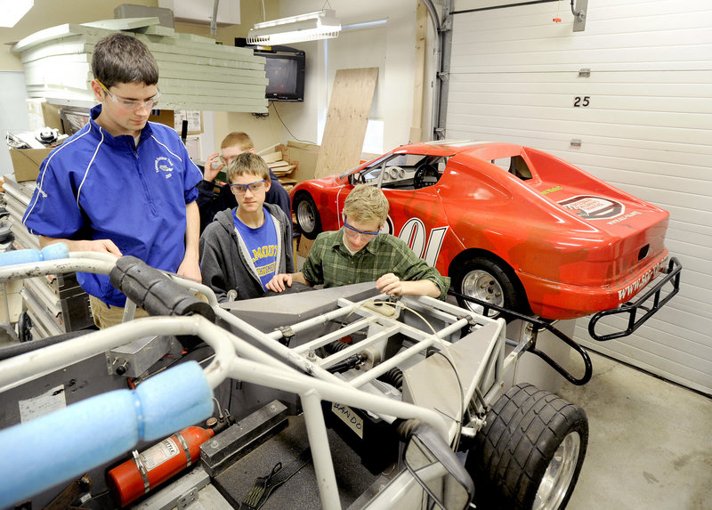 Joe Conway, left, Jamie McCatherin and Tim Follo, right, examine one of the race cars their advanced engineering class is working on. The gas-powered car will race the electric one in a later stage of the class's work.