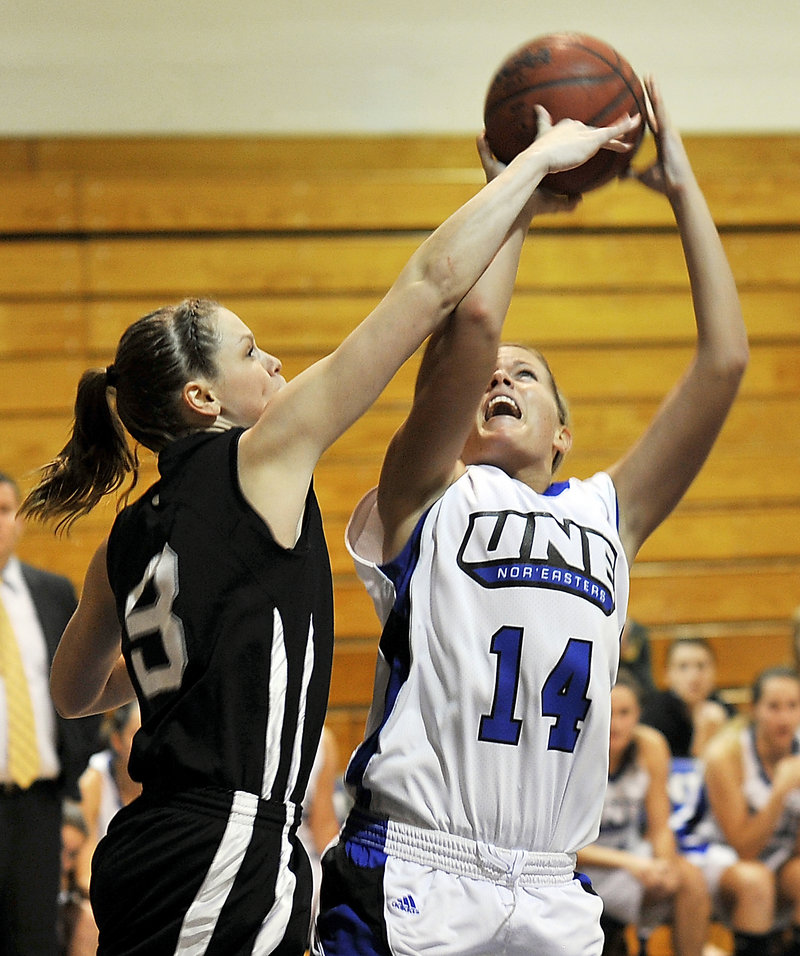 Amy Hackett of Bowdoin, left, blocks a shot by Kelley Paradis of the University of New England during their women's basketball game Tuesday night. Bowdoin's defense led the way to an 82-55 victory.