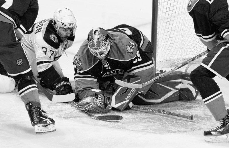 Boston's Patrice Bergeron digs for the puck as Florida goalie Tomas Vokoun covers to prevent a rebound in the first period of the Bruins' 3-1 come-from-behind victory Wednesday at Sunrise, Fla.