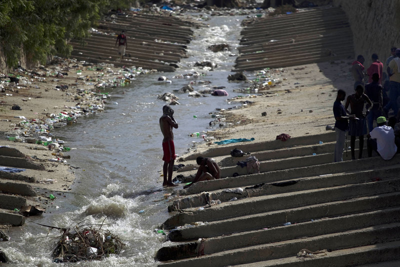 A man bathes in a canal filled with garbage in Port-au-Prince, Haiti, on Monday.