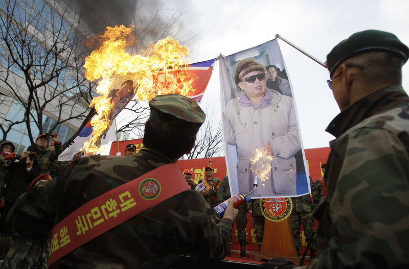 South Korean former marines burn images of North Korean leader Kim Jong Il, right, and his son Kim Jong Un during a rally denouncing North Korea, Saturday in Seoul.