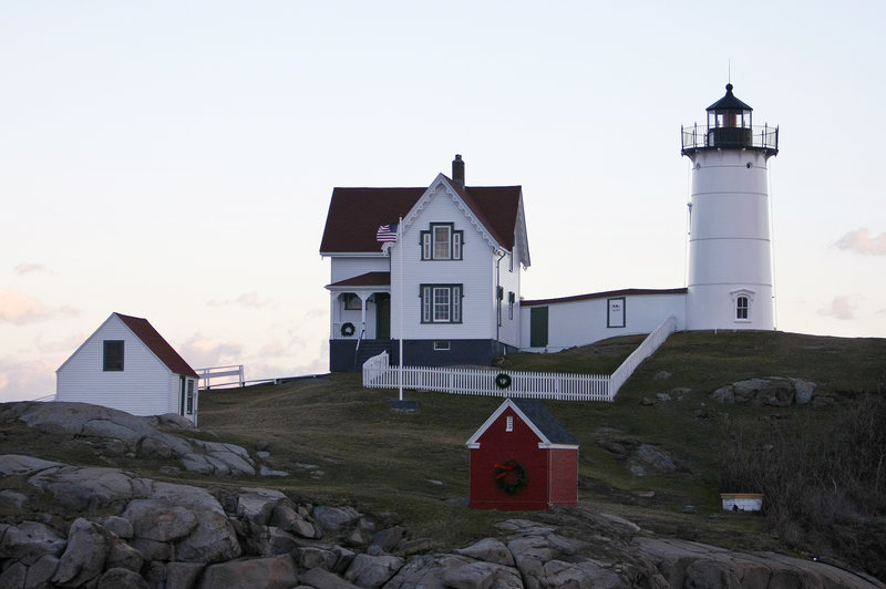 The Cape Neddick Light, on an island off of York, wears its seasonal finery on Saturday, but its holiday lights had to wait to shine.
