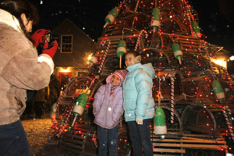 Karen Bonner of Plainville, Mass., takes a photo of her daughters, Jaclyn, 6, and Jessica, 10, in front of a lobster-trap Christmas tree at Sohier Park in York on Saturday.