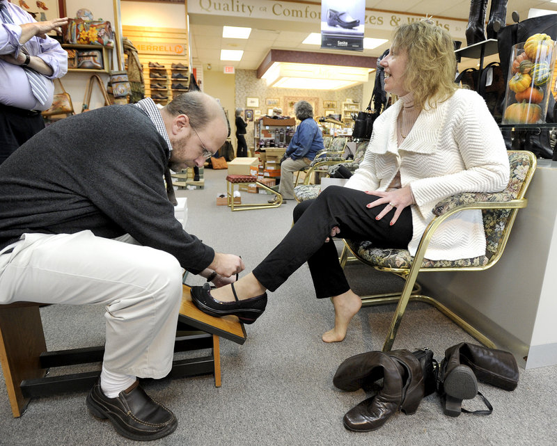 Reporter Ray Routhier buckles a shoe for Marie Forbes of Hampton Beach, N.H., at Selby Shoes, Etc.