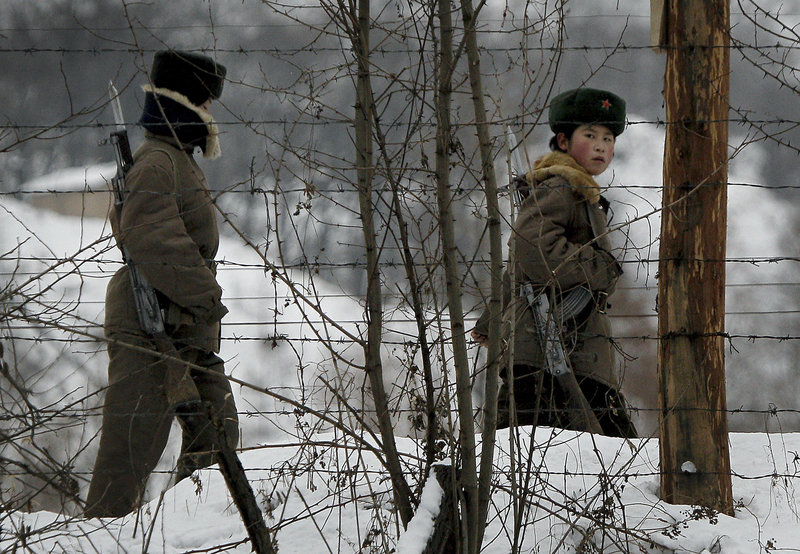 A North Korean female soldier, right, looks back Sunday as she and another patrol on a pathway along the bank of the Yalu River, the China-North Korea border river, near North Korea's town of Sinuiju, opposite the Chinese border city of Dandong.