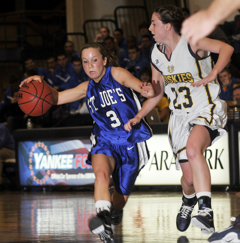 Mackenzie Dufour of St. Joseph's drives down court as Erin McNamara of the University of Southern Maine defends Sunday night in Gorham. The Huskies (2-2) pulled away for a 70-48 victory over the Monks (2-2).